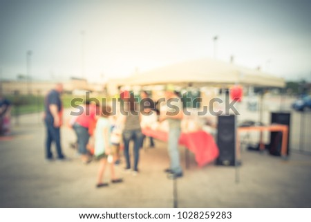 Blurred group of people enjoy barbecue at community event in Houston, Texas, USA. Defocused lunchtime cookout, tent outdoor party and festival concept. Vintage tone