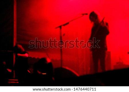 Blurred guitarist playing in red stage lights