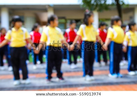 Blurred happy kids holding hands for playing and dancing in the park on the green grass  #559013974