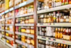 Blurred high shelves with bottles of alcoholic drinks in a large grocery supermarket. Basic background for design