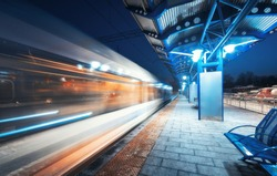 Blurred high speed train on the railway station at night in Europe. Urban landscape with modern passenger train in motion on the railway platform with illumination. Intercity vehicle. Railroad travel