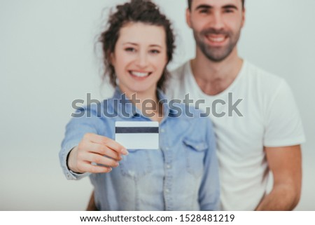 Blurred husband is hugging his wife. Pretty wife is holding a credit card in front of the camera. They are smiling. Focus on the card. #1528481219