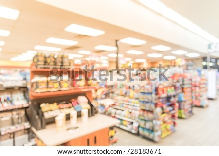 Blurred image a modern convenience store gas station in Arkansas, USA. Variety items on display such as impulse snacks, energy drinks, coffee, hot food, tobacco, cigarettes, clothes, lottery tickets #728183671