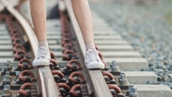 Blurred image, a young woman walks alone down a railroad and towards the destination she had intended. Young tourists happily strolling on the railway alone in the evening