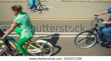 blurred image. Bicycle road sign and bike rider are on bicycle lane. female and male cyclist rides on the bike path parallel to streets. The concept of urban transport and traffic #626351186