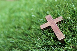 Blurred image. Christian crosses made of wood on a green background.