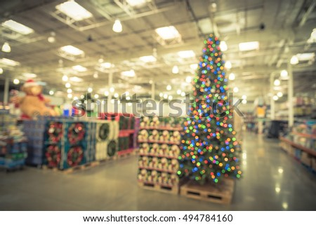 blurred image huge christmas tree decoration in wholesale store wreaths and strings of bokeh light