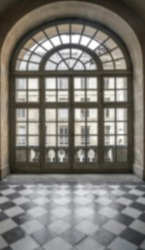 Blurred image. interior with patterned floor and stoned walls with big round window. historical interior. Louvre, Paris