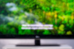 Blurred image of a television screen with a green nature documentary and subtitles