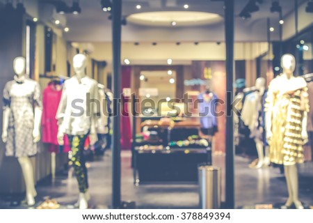 Shutterstock Blurred image of boutique display window with mannequins in fashionable dresses for background. Toned image.