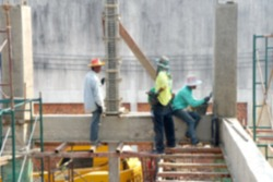 Blurred image of construction workers are working on the beams and columns of the building.