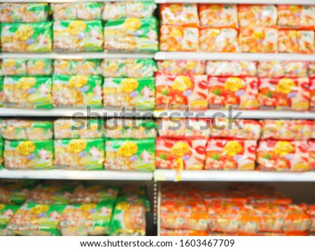 Blurred image of Dry food and instant noodles on shelves, Department store with bokeh blurred background, Abstract blurred supermarket shelf with Dry food and instant noodles as background.