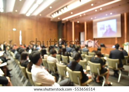 Blurred image of education people and business people sitting in conference room for profession seminar and the speaker is presenting new technology and idea sharing with the content activity.