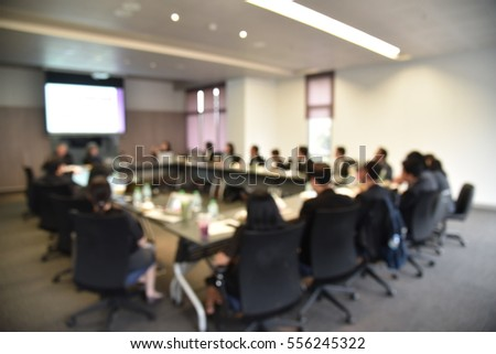 Blurred image of education people and business people sitting in conference room for profession seminar and the speaker is presenting new technology and idea sharing with the content activity project.
