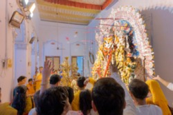 Blurred image of flowers thrown and Pushpanjali being offered by Hindu devotees to Goddess Durga at Shobhabazar Rajbari , bonedi barhir pujo. Durga Puja festival. Kolkata, West Bengal, India.