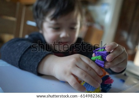 Blurred image of happy kid face playing with plasticine at home, cute kid learning to use colorful of clay                                 #614982362
