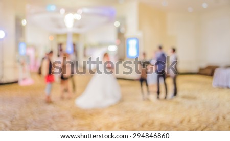 blurred image of Large dining table set for wedding, dinner or festival event with beautiful lights decoration inside large hall with people.