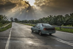 Blurred image of Malaysian National Car, Proton Saga moving ahead on an empty road inside oil plam plantation with sun ray of light as background