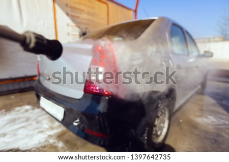 Blurred image of manual car wash with pressurized water in car wash outside. Concept of summer car washing and cleaning car using high pressure water. #1397642735