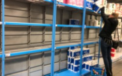 Blurred image of people hoarding products in the supermarket. Supermarket shelves are almost empty due to Coronavirus. Woman takes out toilet paper packaging. The Netherlands. Out of stock