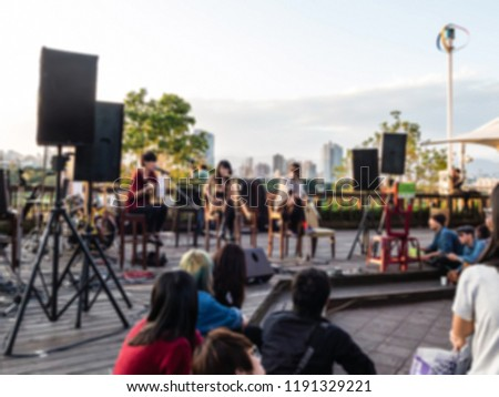 Photo of Blurred image of people listening to an outdoor concert. Performance of a music band outdoor. Outdoor concert.
