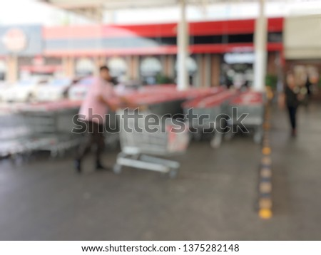 a2e73b74f44 blurred image of people taking a shopping carts or Trolley in a row to buy  food