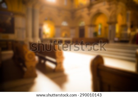 blurred image of pews and alter in typical Catholic church