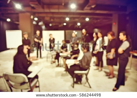 blurred image of production team is sitting and standing, the chairman is talking with the business project in television studio station. vintage filter tone colour