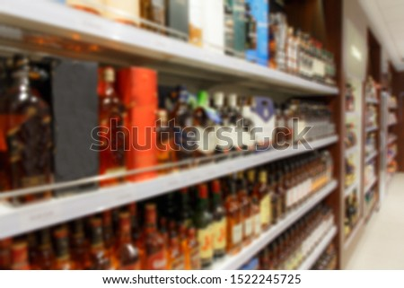 Photo of Blurred image of shelves with alcoholic beverages in the duty free shop Bela Market Duty Free.