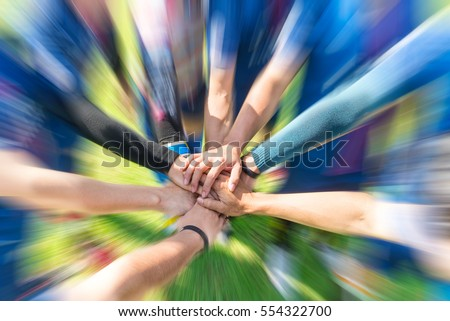 Blurred image of Soccer players putting their hands together Join team energy for power that makes winners