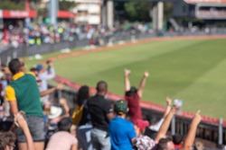 Blurred image of spectators cheering at cricket match