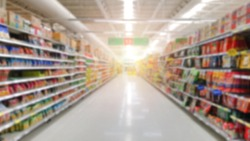 Blurred image of supermarket aisle and shelves.defocused blurry background with bokeh light in store. Business concept.