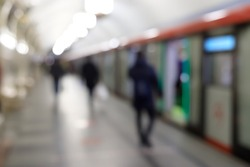 Blurred image of the metro station with people and passenger standing, abstract background blurred image, people hurry at the railway.