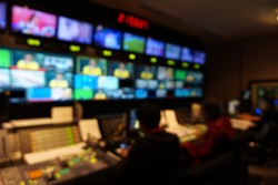 Blurred image of the TV production team in the broadcast control room, which includes video switch and audio mixer, control broadcasts in recording studio.