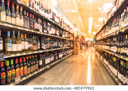 Blurred image of wine shelves display in supermarket. Defocused  Rows of Wine Liquor bottles on the store shelf. Alcoholic beverage abstract background. Alcohol drink market concept. #485979961