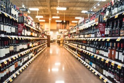 Blurred image of wine shelves with price tags on display at store in Houston, Texas, US. Defocused rows of Wine Liquor bottles on the supermarket shelf. Alcoholic beverage abstract background.