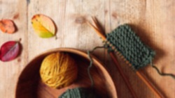Blurred image of wool yarn in a container and knitting needles on a brown wooden table, as well as small sheets of knitted fabric.