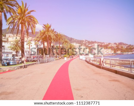 Blurred image, outdoor people walk on the pedestrian concrete landscape in city street with red carpet in summer, italy landscape with red carpet in genoa rapallo vacation concept vintage background.