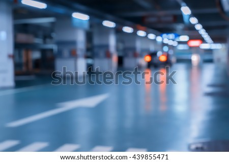 Blurred image/ Parking garage - interior shot of multi-story car park, underground parking with cars.