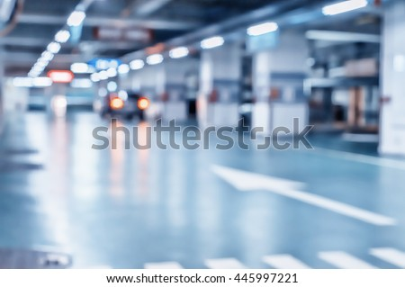 Photo of Blurred image/ Parking garage - interior shot of multi-story car park, underground parking with cars.