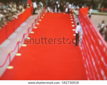 Blurred image. Red carpet entrance with golden stanchions and ropes. Celebrity nominees go to the premiere. Stars on the festive awarding of prizes awards