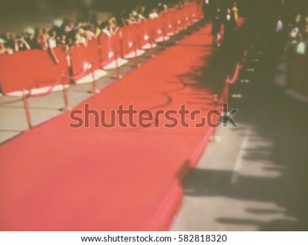 Blurred image. Red carpet entrance with golden stanchions and ropes. Celebrity nominees go to the premiere. Stars on the festive awarding of prizes awards. Vintage style