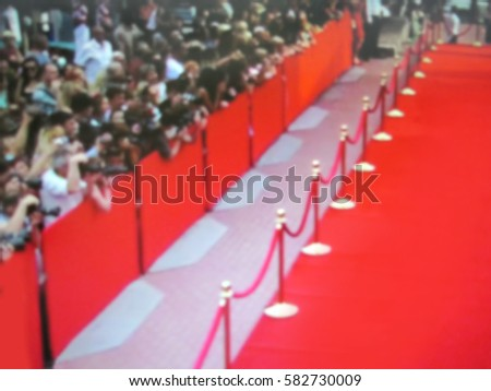 Blurred image. Red carpet entrance with golden stanchions and ropes. Stars on the festive awarding of prizes awards