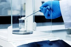 Blurred image, the scientist is weighing the sample for analysis. Laboratory work concept