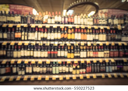 Blurred image wine shelves with price tags on display at store in Humble, Texas, US. Defocused rows of Wine Liquor bottles on supermarket shelf. Alcoholic beverage abstract background. Vintage tone #550227523
