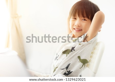 Blurred images of good-humored children who are doing homework in a white room.Children draw pictures on a white table.Children smile freshly