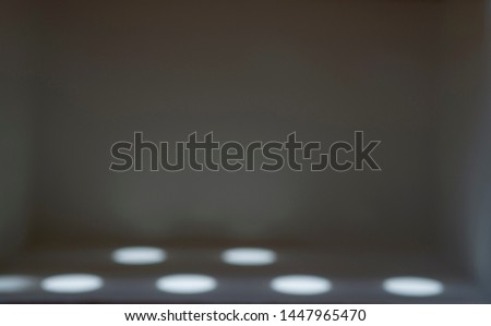 Blurred images of shining and shining beam on the background in a gray room with empty space. #1447965470
