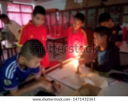 Blurred images of students are doing optical experiments, group process learning, cooperative learning, hands-on learning, Active learning.