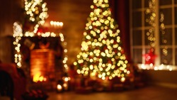 blurred interior christmas. magic glowing tree, fireplace, gifts in  dark at night