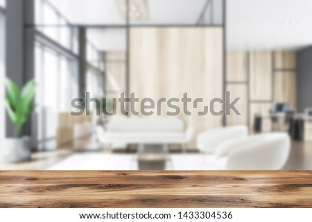 Blurred interior of office waiting room with gray and wooden walls, comfortable armchairs and sofa near coffee tables and open space area in background. Table for your product. 3d rendering